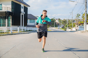 Handsome runner checking his smart watch during a workout in the street