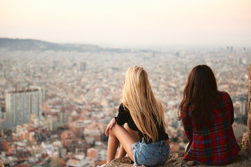 Two young girlfriends sitting against of summer cityscape
