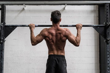 Man doing pull-ups in a gym. view from behind