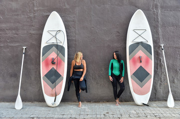 Two friends with their paddle boards on a black wall in Barcelona beach