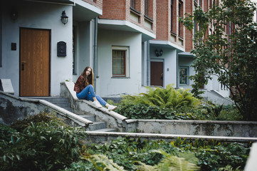 street portrait of a female student in fashionable clothes, blue jeans and a brown jacket, outdoors