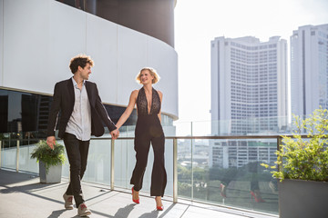Handsome and stylish young couple holding hands and walking on a city balcony