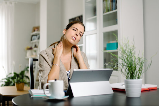Tired female freelance neck pain headache while working from home with convertible tablet. Bad posture using laptop concept.