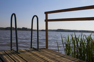 summer evening panorama of lake with railings for swimmers, Latvia