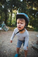 Upset toddler boy with helmet on