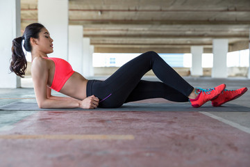 Beautiful and fit young woman doing sit-ups on a gym mat in a concrete urban environment