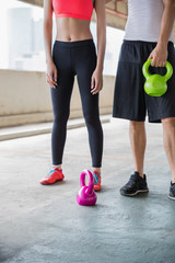 Closeup of two young people working out with kettlebells