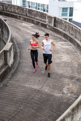 Young man and woman running together in the city