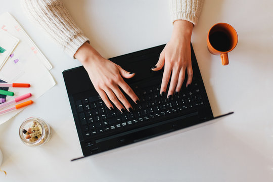 Female hands on a laptop from above