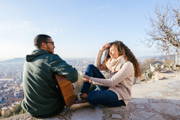 Man sitting playing guitar with his girlfriend above cityscape.