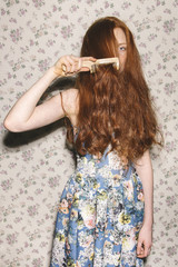 Young red-headed woman combing her hair