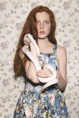 Red-headed young woman holding white snake