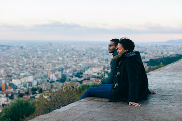 Side view of couple sitting above city at sunrise.