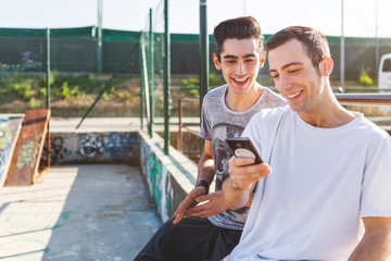 Two Young Friends Having Fun with a Smart Phone at the Skatepark