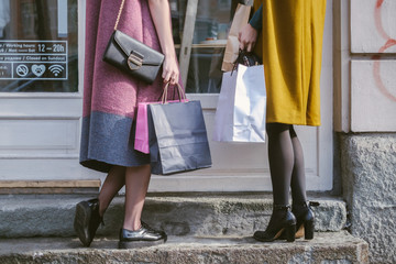 Close up of a Two Women with Shopping Bags Standing in Front of the Shop Window