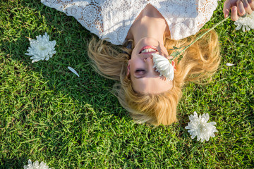 Beautiful smiling blonde lying on grass and covering her eye with a white flower