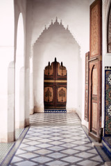 Ornate archway and door with tiled floors in Bahia palace in Marrakech.