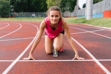 Sprinter woman on the starting block in an athletics track