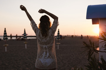 Fashionable woman on the beach at sunset