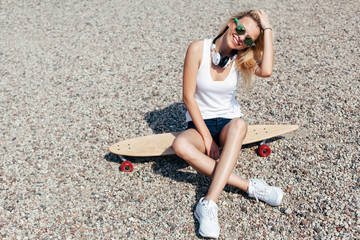 Pretty blonde happy young woman sitting on longboard in summer