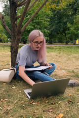 Clever pink-haired girl using laptop in park