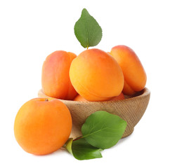 Wooden bowl with fresh apricots on white background