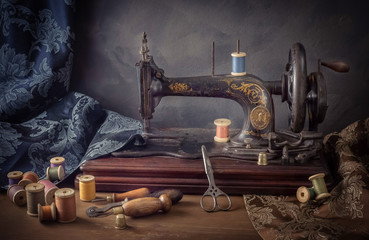 Still life with a sewing machine, scissors, threads