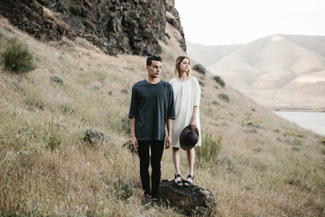 modern fashionable couple posing in desert landscape
