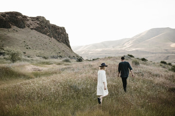 young fashionable couple walking through desert landscape
