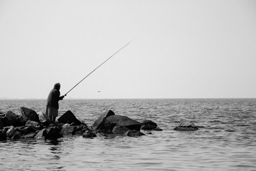 Single old woman is fishing on a stones