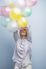 Cheerful girl holding colorful balloons