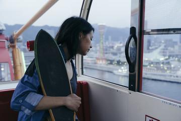 Asian girl looking at panorama from Kobe ferris wheel