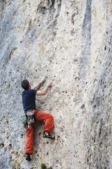 Rock climber climbing a vertical wall outdoors
