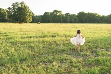 A Young Girl Runs Through An Open Field At Sunset