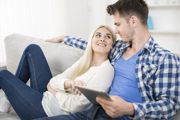 The happy man hold the tablet near the woman on a sofa