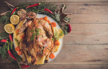 Whole roasted turkey with potatoes on wooden background with blank space