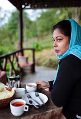 Woman drinking tea on balcony