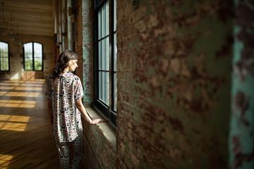 Beautiful woman looking our warehouse window