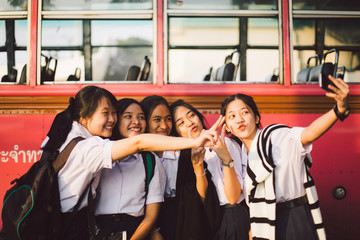 Thai school girl group making selfie together at the bus stop afterschool