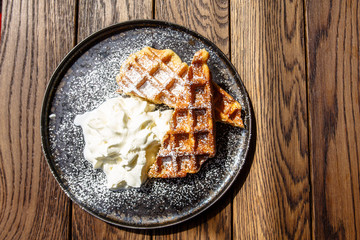Viennese waffles with berry sauce and creme fraiche are on the plate.