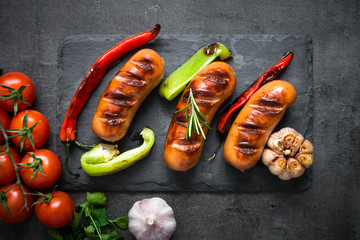Fried bbq sausages with  vegetables at black background. Top view.