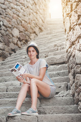 Young woman tourist is sitting on the stairs in the Rabati Fortress and reading brochure