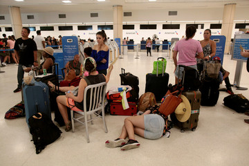 Stranded tourists and Puerto Ricans line up at the International Airport as they try to leave after Hurricane Maria devastated power and communications across the island, in San Juan