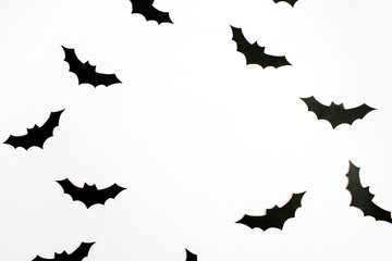 Halloween holiday concept. Handmade black paper bats on white background. Flat lay, top view.