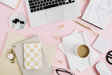 Flat lay modern workspace with laptop, notebook and stationery on pastel pink background. Top view. Golden style lifestyle concept.