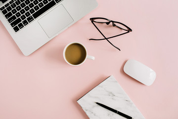 Flat lay lifestyle workspace concept. Minimal office desk with laptop, marble notebook, glasses, mouse and coffee on pastel pink background. Top view.