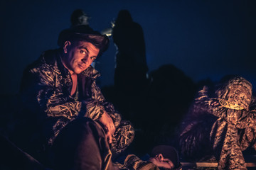 Father and son sitting by the fire in outdoors camp in the night  after long hunting day