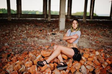 Girl wear on shorts at abadoned factoty sitting on brick.
