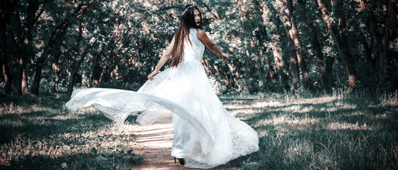 Woman or girl, a bride in a white wedding dress, stands in the middle of a forest or park, a mysterious photo, dress flying