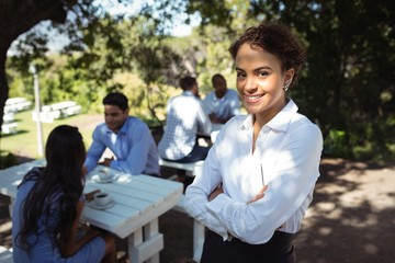 Waitress standing with arms crossed at outdoor restaurant